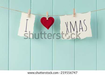"""I love xmas"" hanging on a rope with clothespins. A robin egg blue wainscot as background. Vintage Style. - stock photo"