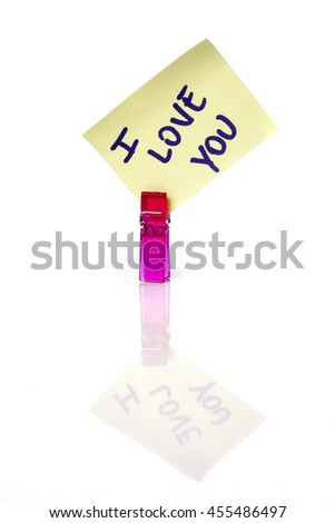 """I love you"" message written on a yellow paper note with a clothespins holding isolated on white background with reflections. - stock photo"