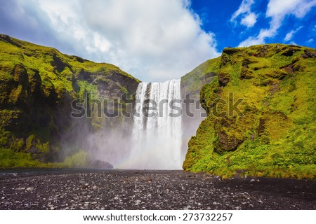 Iceland, waterfall Skogafoss summer, clouds of mist. Huge waterfall flowing from under giant glacier - stock photo