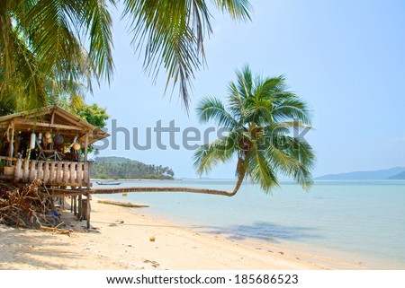 idyllic tropical beach with a little treehouse and palmtrees  - stock photo