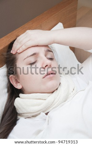 ill woman in bed touching her head - stock photo