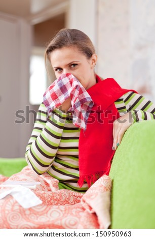 illness woman uses handkerchief in home - stock photo