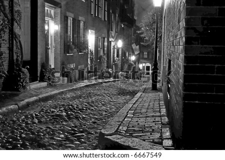 image of an old 19th Century cobble stone road in Boston Massachusetts, lit only by the gas lamps revealing the shuttered windows and brightly lit doorways of the rowhouses on Acorn Street - stock photo