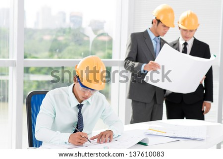 Image of engineers in hardhats working on various construction projects - stock photo