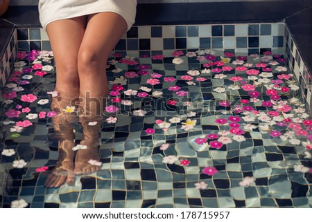 : Image of female feet dipped into spa and aromatherapy bowl on the foreground  - stock photo
