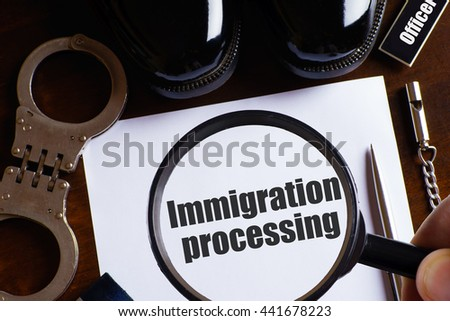 """Immigration processing"" text with a man hold magnifying glass zoom on paper with pen, whistle, handcuff and a pair of black shoes on wooden table - law and enforcement concept - stock photo"