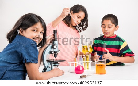 3 indian kids doing science experiment, science Education. asian kids and science experiments, chemistry experiment, indian kids and science experiments, indian kids and science lab - stock photo