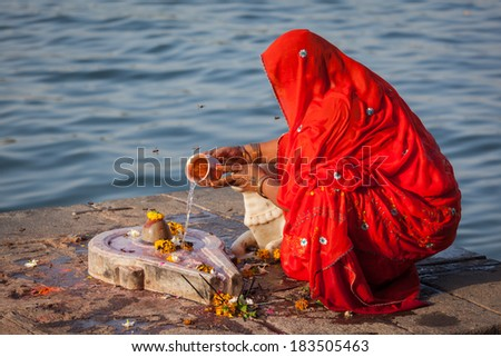 Indian woman performs morning pooja on sacred river Narmada ghats in Maheshwar, Madhya Pradesh, India. To Hindus Narmada is one of 5 holy rivers of India - stock photo