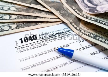 1040 individual tax return form and dollar bils - stock photo