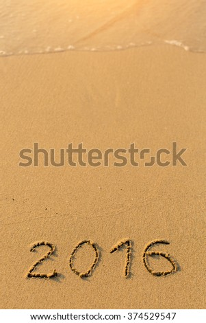 2016 - inscription on sand beach with the soft wave. - stock photo