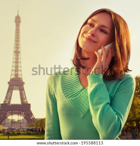 Instagram-like cross processed picture. France with Eiffel Tower in background. Cute beautiful Caucasian female model holding a phone in her hand and smiling.  - stock photo