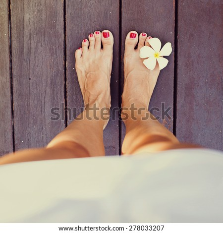 """""""instagram"""" style photo of bare feet standing on a floor. Top view. Filter applied - stock photo"""