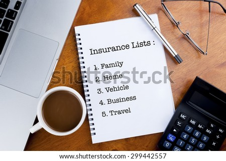 """Insurance Lists with family, home,vehicle,business and travel"" text on notebook with a cup of coffee, calculator, spectacle and laptop on desk - stock photo"