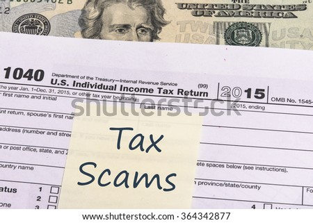 2015 Internal Revenue Service form 1040 close up detail with United States currency and reminder note. Tax season is January to April. - stock photo