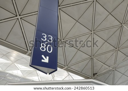 25 January 2014, Hong Kong International Airport Signage on Triangular Background Directing to Gates 33 to 80 at Hong Kong International Airport - stock photo