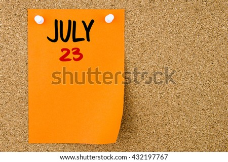 23 JULY written on orange paper note pinned on cork board with white thumbtacks, copy space available - stock photo