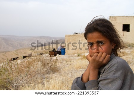 3 June 2014, Madaba, Jordan: bedouin girl by her family's camp on the road from the Dead Sea, to Madaba, Jordan. In the background her father is tending to the herd of goats. - stock photo