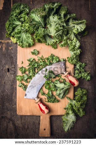 kale chopping on cutting board and old mincing knife, dark wooden background, top view - stock photo