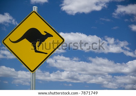 """Kangaroo"" road warning sign against a blue sky background with copyspace to the right - stock photo"