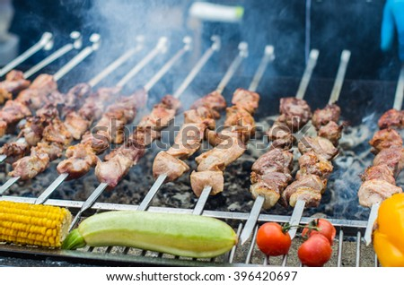 Kebab and tomatoes , zucchini , peppers , corn roasted on the grill skewers . Vegetables and different kinds of meat - lamb , pork, beef , chicken on the street market . Close-up on the coals. - stock photo