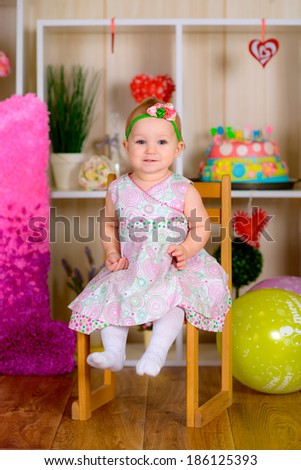 kid in first birthday with colored balloons in the bright room  laughing  - stock photo