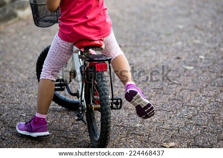 Kid is cycling in the park - stock photo