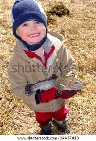Kids fishing - Young boy holding a rainbow trout fish caught fly fishing - stock photo