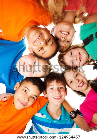 7 kids looking down standing in a circle smiling and looking down - stock photo