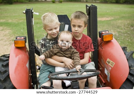 3 kids sitting on tractor - stock photo