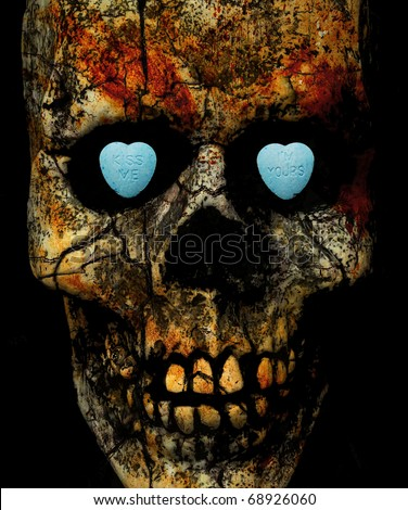 """""""kiss me, I'm yours"""" written on candy hearts inside a textured skull's eye sockets - stock photo"""