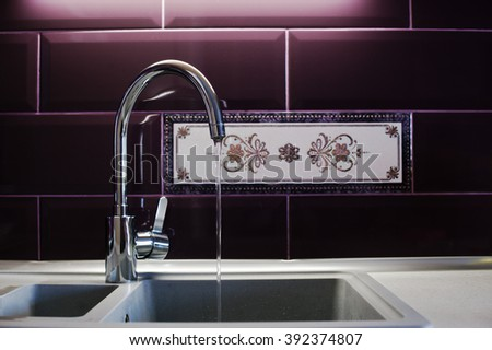 Kitchen mixer tap into granite work with running water - stock photo