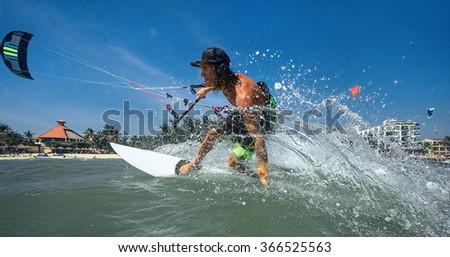 Kitesurfer with board on ocean wave - stock photo
