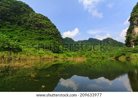 Landscape with mountains and clouds in Van Long Natural reserve of Ninh Binh, Vietnam  - stock photo