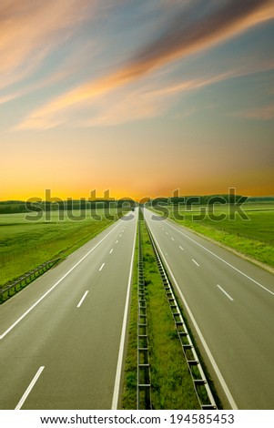 landscape with road and green fields - stock photo