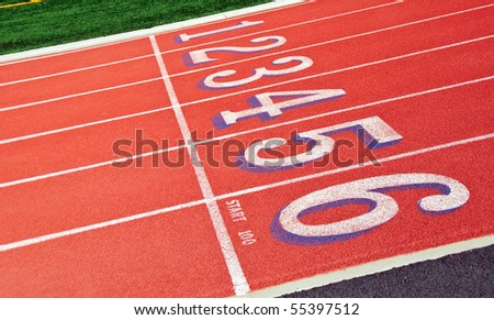 Lanes of a red race track with numbers and green football field - stock photo