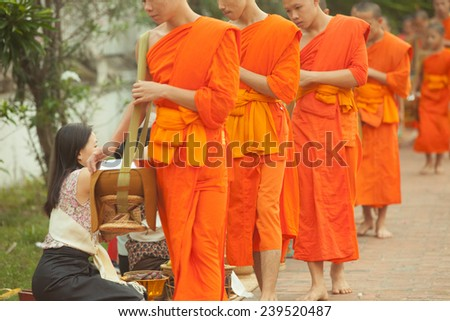 Lao People's Democratic Republic, Luang Prabang - 20 JUNE: People giving alms to buddhist monks on the street,  Luang Prabang, 20 JUNE 2014. - stock photo