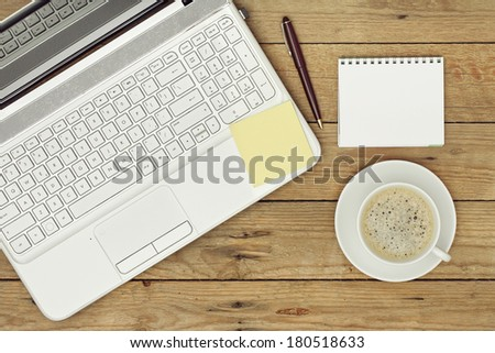 laptop, coffee and notepad on wooden surface - stock photo