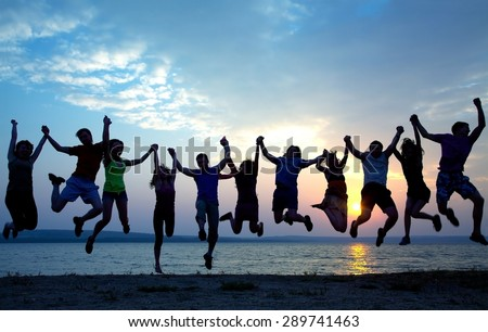 large group of young people having fun and jumping on the beach at sunset - stock photo