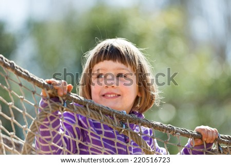 laughing baby girl climbing on ropes at playground area - stock photo
