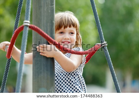 laughing girl climbing at ropes on playground area in summer - stock photo