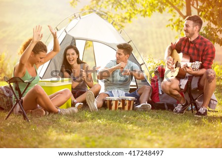 Laughing group of young people enjoy in music of drums and guitar on camping trip - stock photo