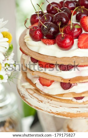 Layer cakes with protein cream and fresh cherry and berries on a cake stand outdoors - stock photo