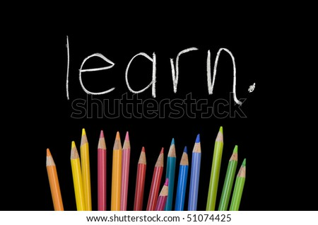 """""""learn"""" written on chalkboard with rainbow colored pencil crayons - stock photo"""