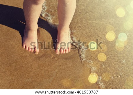 Legs of children stand on the beach - stock photo
