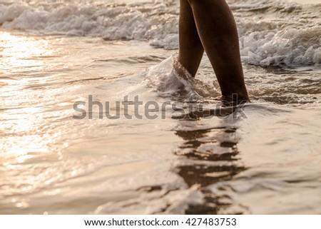 Legs walking on the beach - stock photo