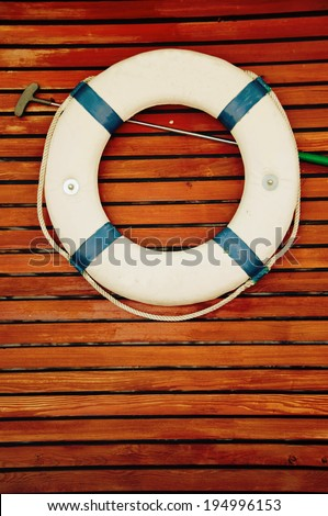 Life buoy hanging on the side of a wooden ship  - stock photo