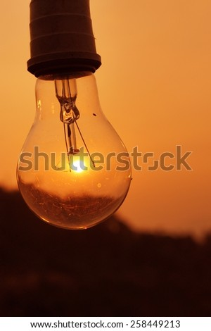 Light bulb with sunset time - stock photo