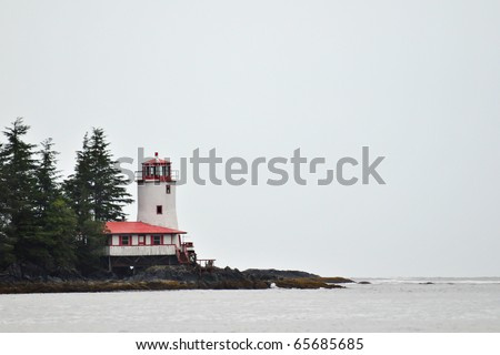 lighthouse on sound near sitka alaska in foggy conditions - stock photo