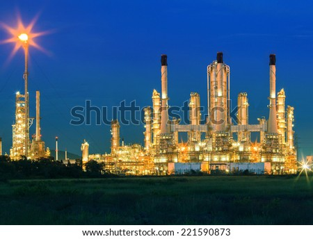 lighting of oil refinery plant against dusky blue sky of oil refinery plant in heavy petrochemical industry estate  - stock photo