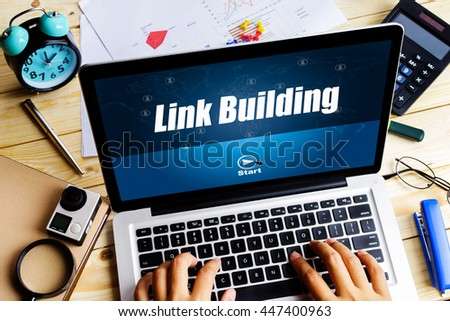 """""""Link Building"""" word on screen laptop with man hand work on it on wooden table with camera, spectacles, clock, pen and calculator - business, website, travel and blogging concept - stock photo"""